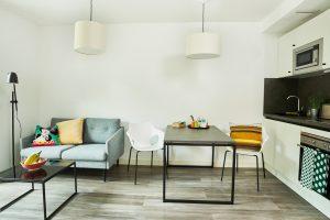 Wohnbereich mit Sofa, Esstisch und Küchenzeile in einem Apartment in der Urban Base in Wiesbaden