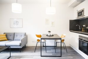 Innenansicht mit Sofa, Couchtisch, Esstisch und Küchenzeile in einem Apartment in der Urban Base in Wiesbaden