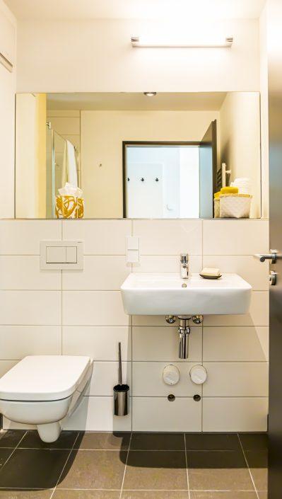 Toilette, Waschbecken und Spiegel in einem Badezimmer eines Apartments in der Urban Base in Wiesbaden