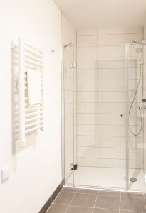 Dusche und Handtuchwärmer in einem Badezimmer in einem Apartment in der Urban Base in Wiesbaden