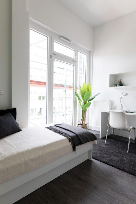 Bett und Schreibtisch in einem Apartment im Barton Living der Cube Real Estate