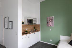 Küchenzeile und Bett in einem Apartment im Barton Living der Cube Real Estate